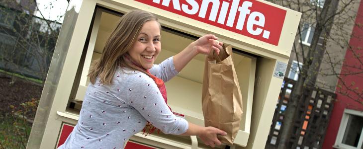 Frau wirft Sack mit Kleidung in einen Volkshilfe Textilsammelcontainer