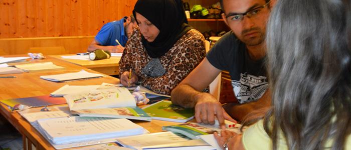 Flüchtlinge mit ihrer Lehrerin beim Deutschlernen