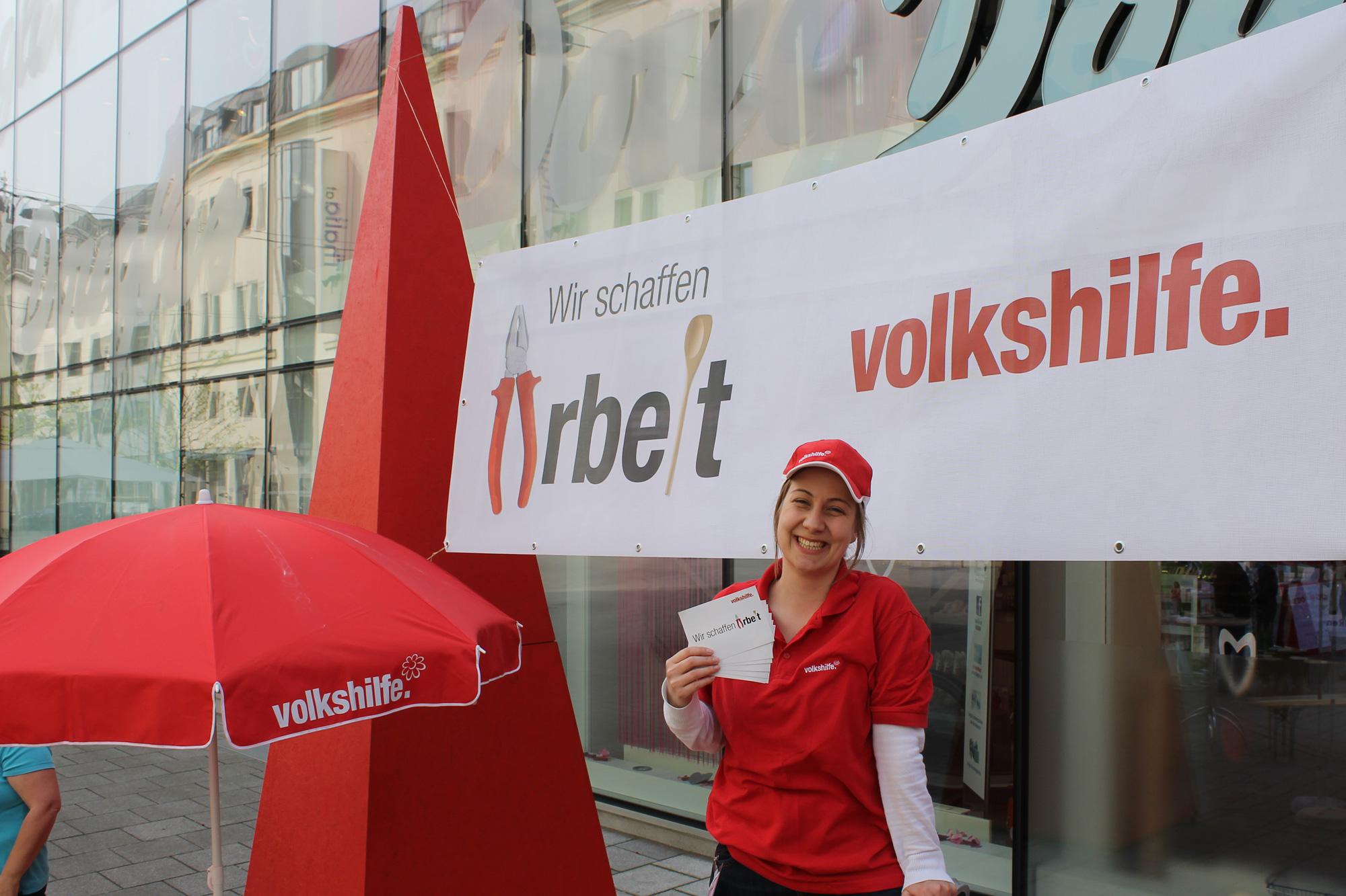 """Eine Mitarbeiterin der Volkshilfe vor einem Transparent """"Wir schaffen Arbeit"""", im Hintergrund die 4 Meter hohe, rote Arbeitslosen-Pyramide"""